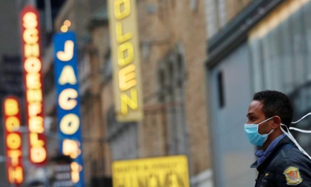 FILE PHOTO: A man in a surgical mask walks through Manhattan's Broadway Theatre district after Broadway shows announced they will cancel performances due to the coronavirus outbreak in Manhattan, New York City, New York, U.S., March 12, 2020. REUTERS/Andr
