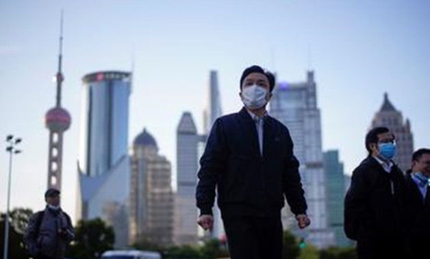 FILE PHOTO: FILE PHOTO: People wear protective face masks, following an outbreak of the novel coronavirus disease (COVID-19), at Lujiazui financial district in Shanghai, China March 19, 2020. REUTERS/Aly Song - RC22NF9MD3D3/File Photo/File Photo