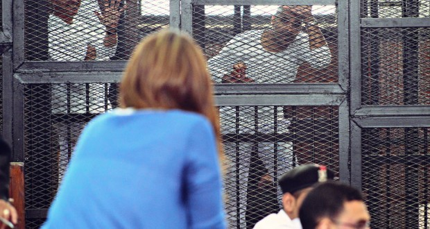 Al Jazeera English Journalist Mohamed Fadel Fahmy tries to talk to his fiance during his trial from behind the cage bars at the makeshift courtroom at the Police NCO's Academy while colleague Peter Greste waves to journalists behind him. Photo Credit: Amir Makar.