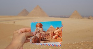Alana at the pyramids with a postcard she received from a childhood friend years ago.