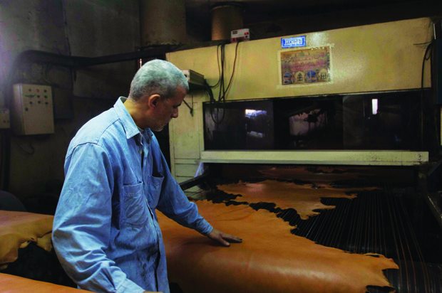 A worker feeds the tanned hides into a machine for extra color.